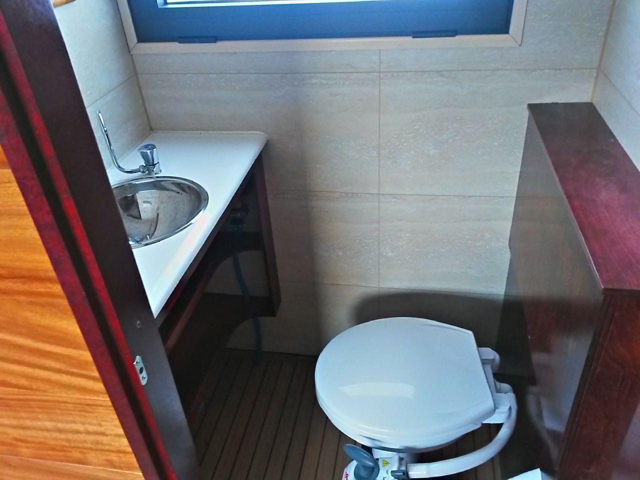 Blick in die WC Kabine mit Waschbecken und fließend kaltem Wasser.