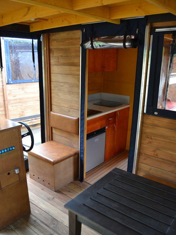 Blick von der Terrasse über den Fahrersitz in den Küchenbereich im inneren des Floßes mit Kühlschrank, Gasherd und Spülbecken.