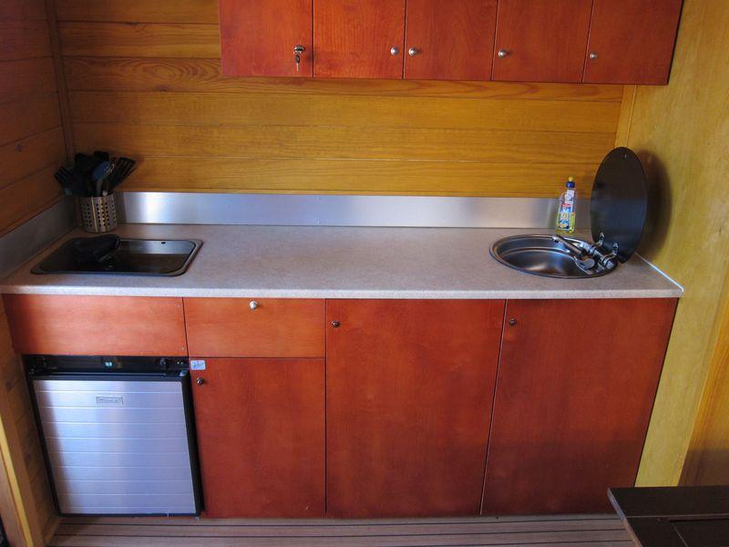 2,00m Arbeitsfläche mit Gaskühlschrank, 2-flammigen Gasherd, Spüle mit fließend kaltem Wasser und umfangreichem Ess- und Kochgeschirr.