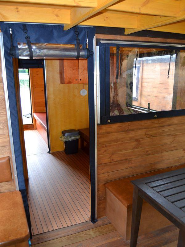 Blick von der Terrasse ins Floß. Im ersten Raum sieht man die Ausziehcouch im zweiten Raum das französische Bett.