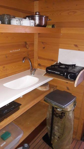 Das Küchenregal mit Campinggaskocher und kleiner Spüle.