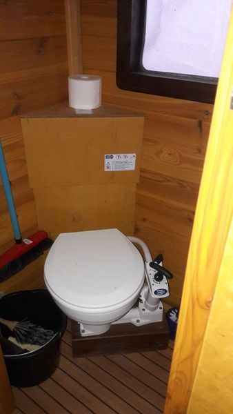 Die WC-Kabine mit fester Toilette mit Handpumpe